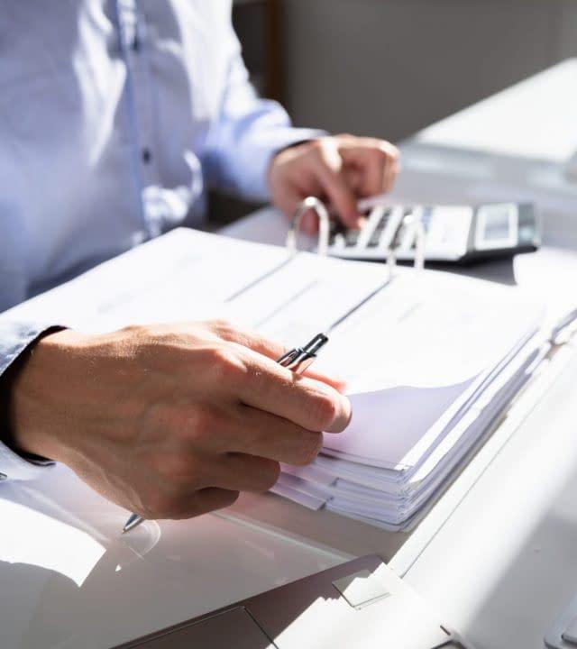 Businessperson Calculating Invoice Using Calculator At Desk